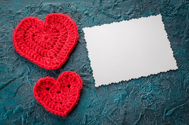 Crochê os corações dos namorados e o cartão em fundo escuro.