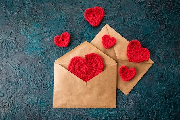 Crochê os corações dos namorados e o envelope na superfície escura.