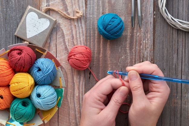 Crochê, vista superior nas mãos com bolas de gancho e fios de crochê, vista superior em madeira rústica