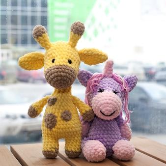 Crochet amigurumi amarelo girafa e unicórnio. brinquedo artesanal de malha.