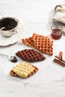 Croffle croisant waffle com várias coberturas, queijo, chocolate, açúcar e canela. croffle é comida de rua viral da coreia. copiar espaço