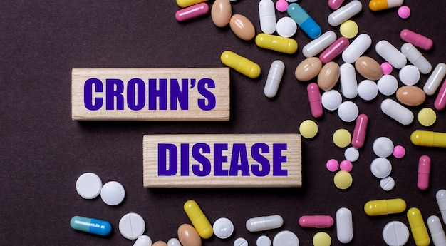 Crohns disease está escrito em blocos de madeira perto de pílulas multicoloridas.