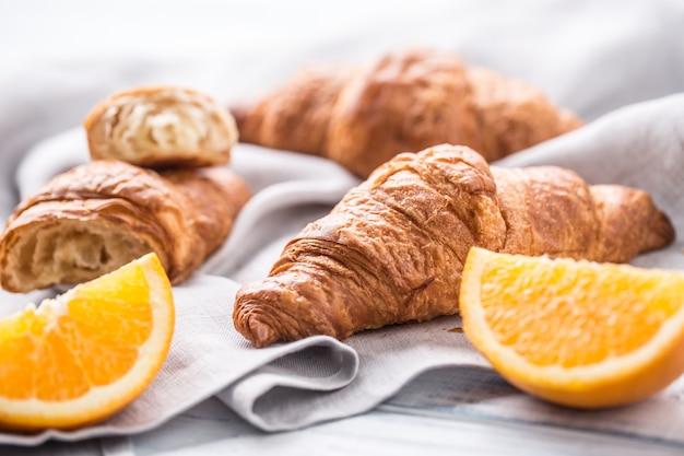 Croisants amanteigados frescos com laranjas doces em guardanapo de cozinha.