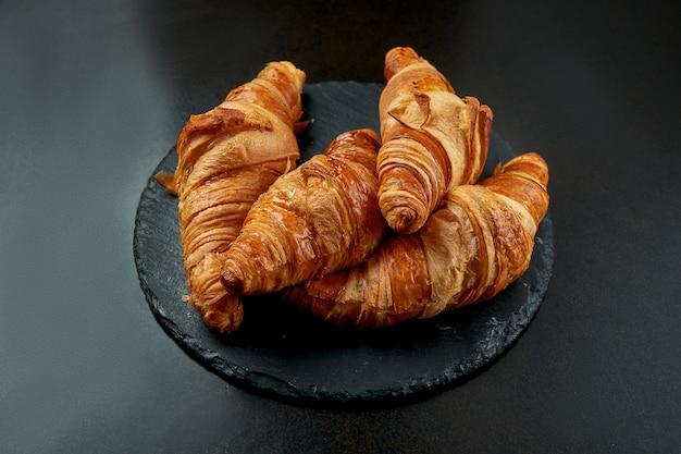 Croissant assado apetitoso em um fundo escuro. pastelaria francesa