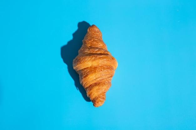 Croissant assado de produtos de panificação. fundo azul, vista superior. estilo pop art. delicioso e conceito de comida.