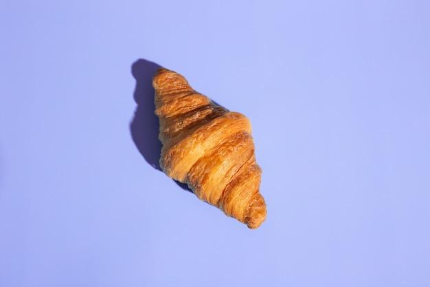Croissant assado de produtos de panificação. fundo roxo, vista superior. estilo pop art. delicioso e conceito de comida.