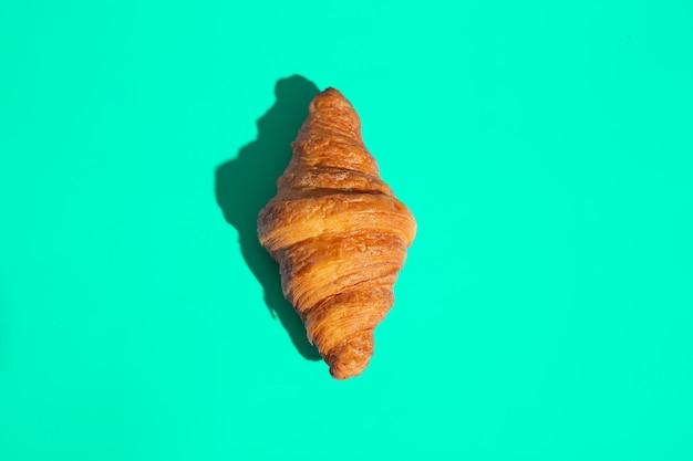 Croissant assado de produtos de panificação. fundo verde, vista superior. estilo pop art. delicioso e conceito de comida.