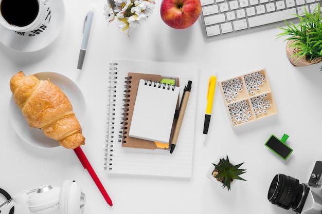 Croissant assado; xícara de chá e maçã com artigos de papelaria na mesa branca