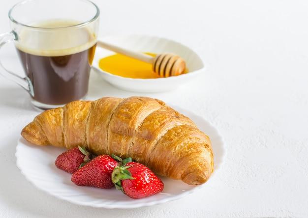 Croissant, café e morango. conceito de pequeno-almoço de verão.