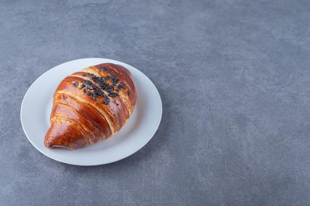 Croissant caseiro com chocolate no prato, no mármore.