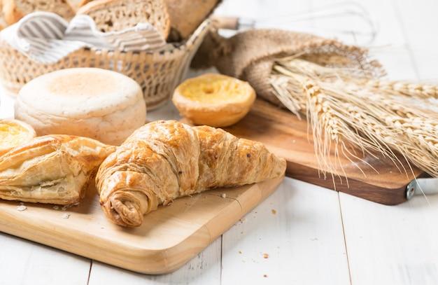Croissant caseiro com torta e muffin inglês em bloco de madeira, padaria fresca