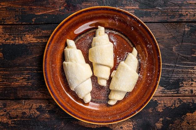 Croissant caseiro cru cru em um prato rústico. fundo de madeira escuro. vista do topo.