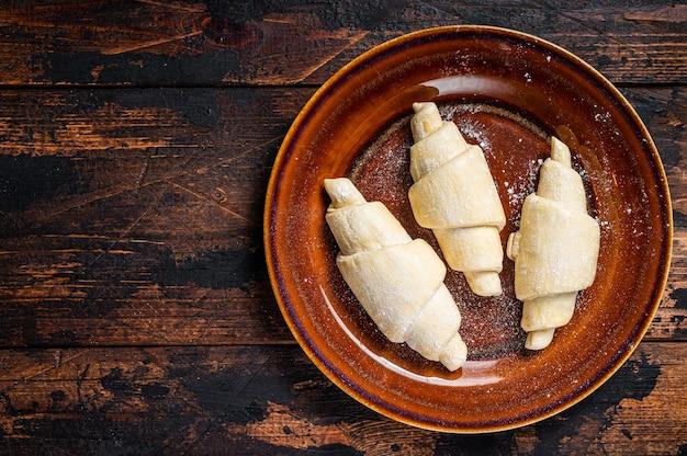 Croissant caseiro cru cru em um prato rústico.
