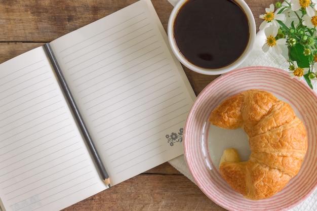 Croissant caseiro no prato servido com café preto ou americano no café da manhã