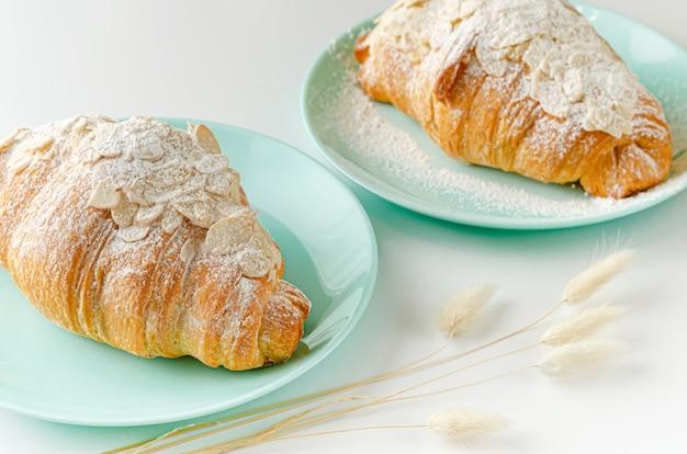 Croissant com açúcar em pó e flocos de amêndoa