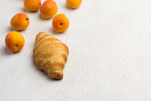 Croissant com alperce fresco. saboroso café da manhã. fundo branco. vista do topo. copie o espaço