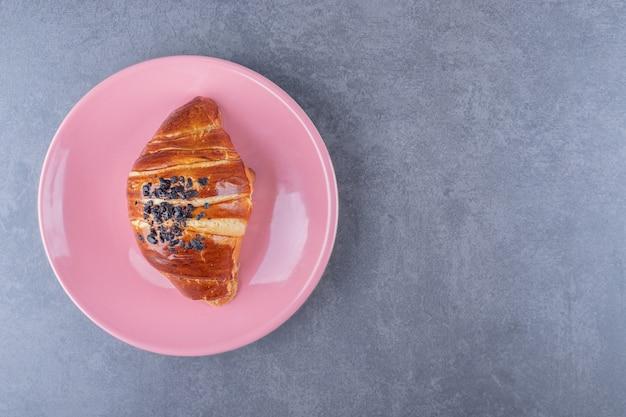 Croissant com chocolate no prato, no mármore.