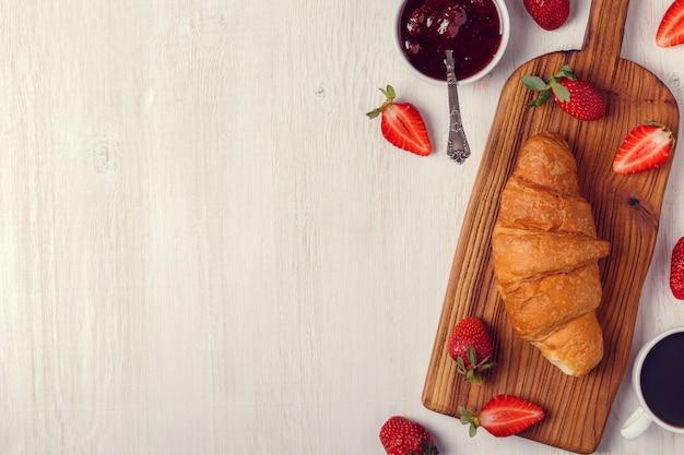 Croissant com geléia de morango em uma placa de madeira