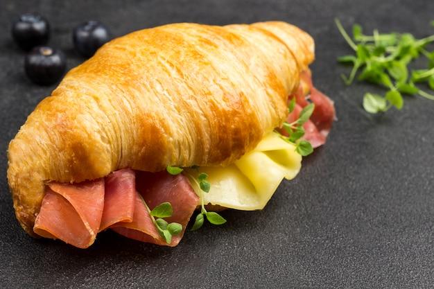 Croissant com jamon e queijo e verduras. superfície preta. vista do topo