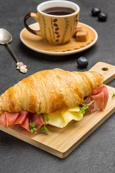 Croissant com jamon e queijo e verduras. xícara de café. superfície preta.