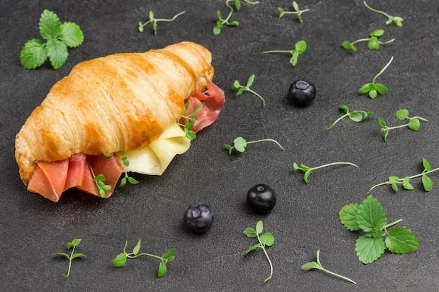 Croissant com jamon e queijo. xícara de café. verduras na mesa. superfície preta.