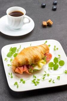 Croissant com jamon, queijo e verduras na chapa branca. xícara de café. superfície preta.