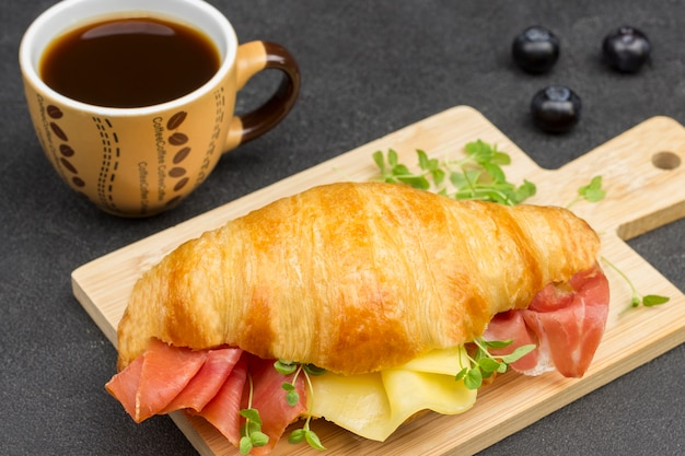 Croissant com jamon, queijo e verduras na tábua. xícara de café. vista do topo. superfície preta.