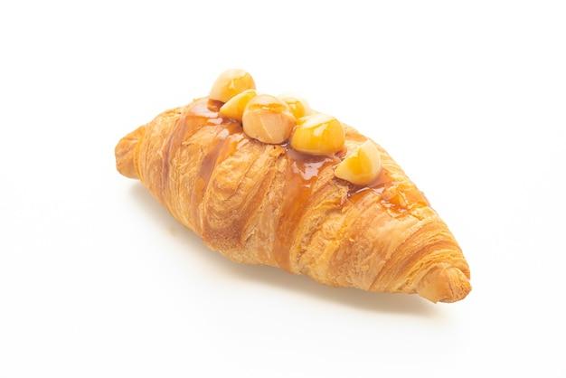 Croissant com macadâmia e caramelo isolado no fundo branco