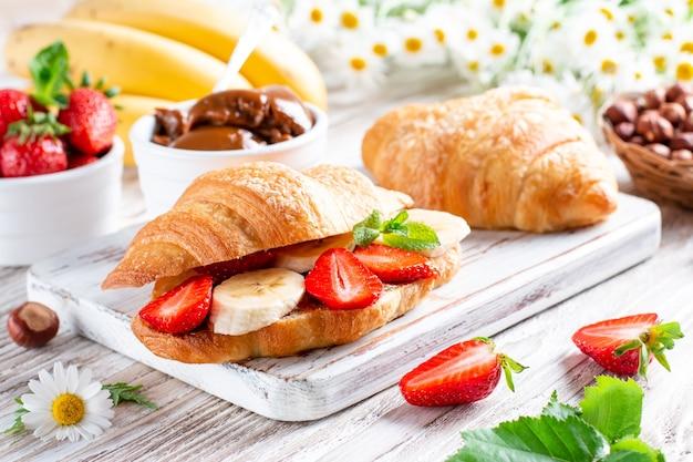 Croissant com manteiga de chocolate, banana e morango na mesa de madeira