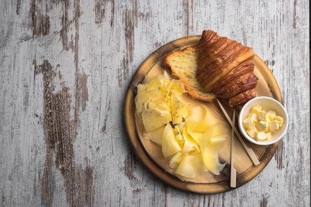 Croissant com manteiga e queijos na mesa velha de madeira vintage branco. lugar livre para texto