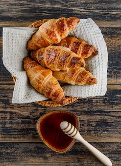 Croissant com mel, dipper em uma cesta na mesa de madeira, plana leigos.