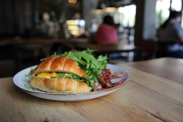 Croissant com ovo e bacon em fundo de madeira