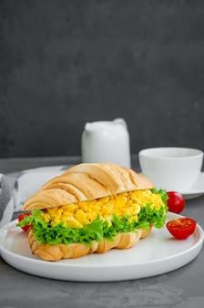 Croissant com ovos mexidos, alface e tomate cereja