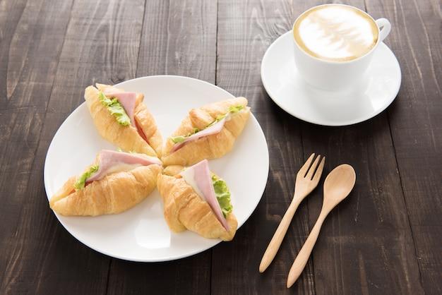 Croissant com presunto de parma e café na mesa de madeira