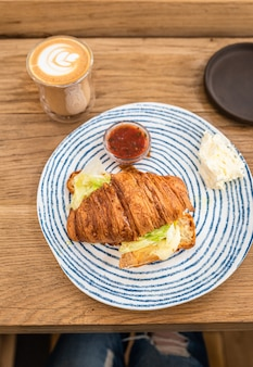 Croissant com queijo grelhado e salada no prato e xícara de cappuccino com latte art, mesa de madeira em um café ou cafeteria