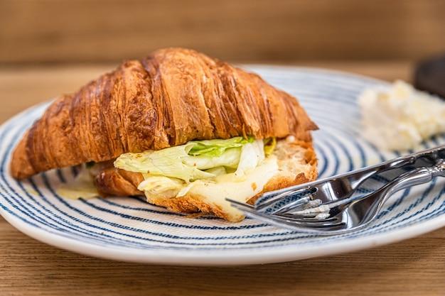 Croissant com queijo grelhado e salada no prato, mesa de madeira em cafeteria ou cafeteria
