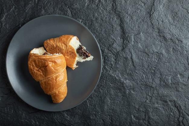 Croissant com recheio de chocolate em um fundo escuro.