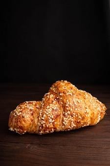 Croissant com sementes de gergelim, isolado em uma mesa de madeira.