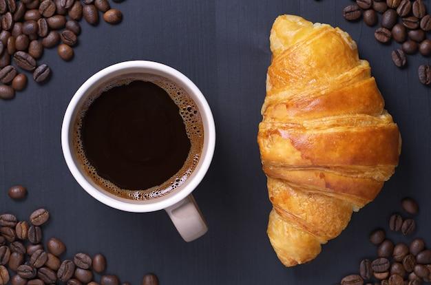 Croissant com uma xícara de café e feijão em um fundo preto de madeira