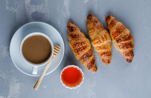 Croissant com xícara de café, mel, concha, vista superior.