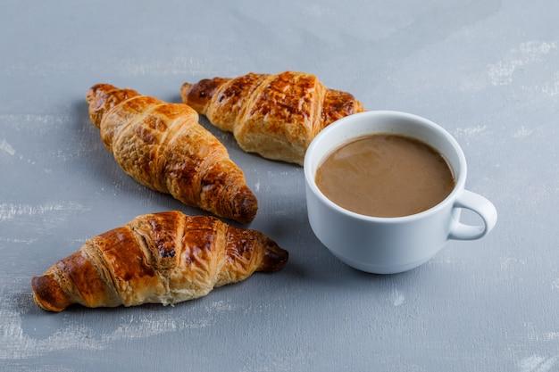 Croissant com xícara de café, vista de alto ângulo.