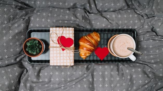 Croissant, coração de ornamento, copo de bebida, planta e caixa de presente na bandeja