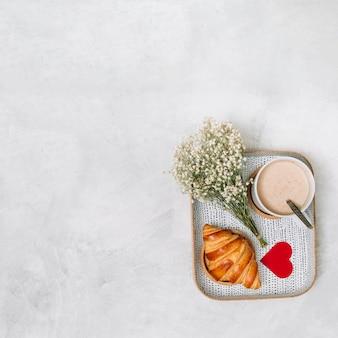 Croissant, coração de ornamento, plantas e copo de bebida na bandeja