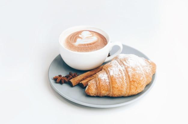 Croissant cozido fresco com arte de xícara e café com leite
