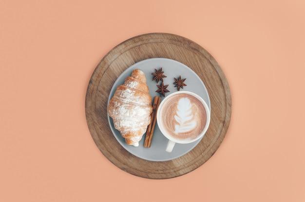 Croissant cozido fresco com xícara de café e especiarias