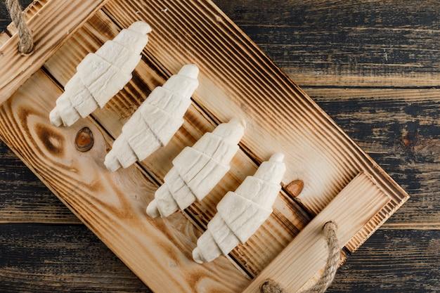 Croissant cru em uma bandeja rústica em uma mesa de madeira. configuração plana.