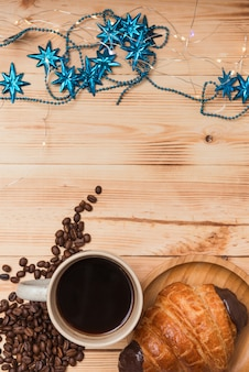 Croissant da xícara de café na tabela de madeira, nas luzes de natal e na decoração azul, vista superior.