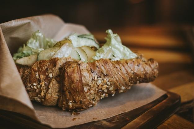 Croissant de café da manhã saudável com salada de gergelim, pepino e pêra em uma mesa de madeira