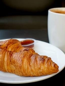 Croissant de manteiga e café quente