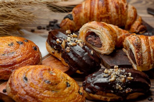 Croissant de massa folhada de chocolate, éclair de chocolate e rolo de passas doces
